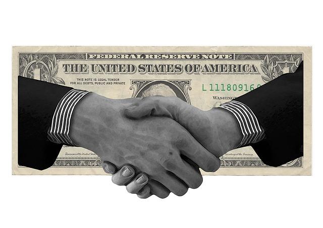 Držící se ruce a dolarovka na pozadí